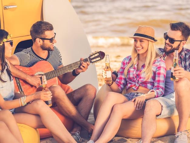 Genieten van de zomer met vrienden. groep jonge gelukkige mensen die samen plezier hebben terwijl ze op het strand in de buurt van hun minibus zitten