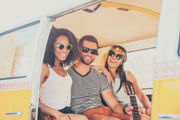 Genieten van de zomer met vrienden. twee jonge vrouwen en mannen hechten zich aan elkaar vast en glimlachen terwijl ze samen in het retro busje zitten