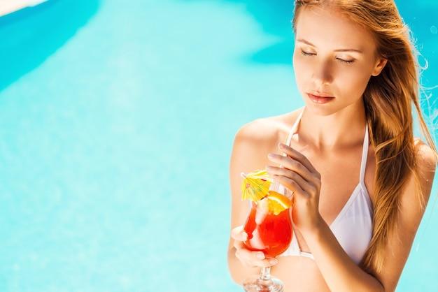 Genieten van de zomer. mooie jonge vrouw in witte bikini die een cocktail vasthoudt en de ogen gesloten houdt terwijl ze aan het zwembad ontspant