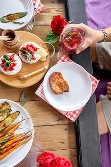 Genieten van een diner man eet, drink limonade, eettafel, verschillende soorten hapjes die thuis op een feesttafel worden geserveerd.