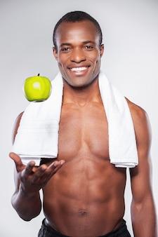 Genieten van een gezonde levensstijl. jonge gespierde afrikaanse man met handdoek op schouder die een appel overgeeft en naar de camera glimlacht terwijl hij tegen een grijze achtergrond staat
