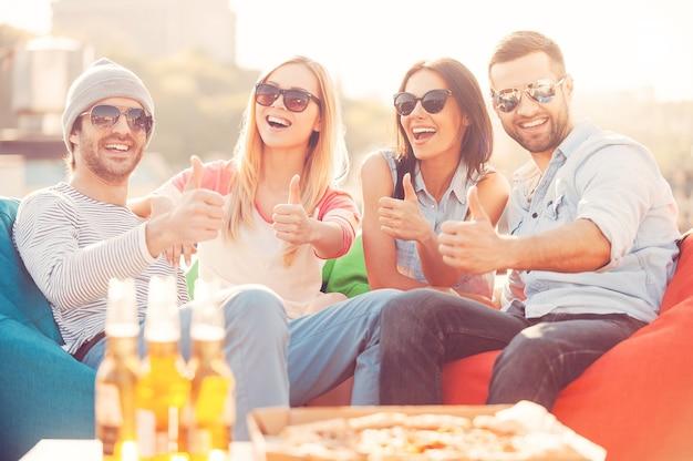 Genieten van een goede tijd. vier jonge vrolijke mensen die hun duimen opsteken en glimlachen terwijl ze op zitzakken op het buitenterras zitten met pizza en bier op de voorgrond