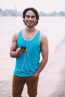 Genieten van een mooie dag buitenshuis. knappe jongeman met koptelefoon die naar de camera kijkt en glimlacht terwijl hij aan de rivier staat met stadsgezicht op de achtergrond