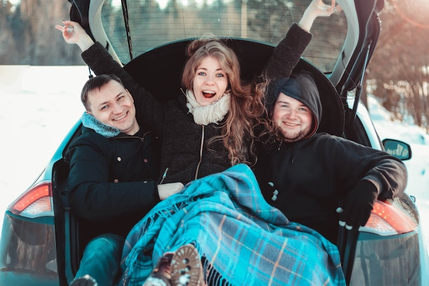 Genieten van een roadtrip met beste vrienden. groep jonge vrolijke mensen die genieten van hun roadtrip in de kofferbak in het winterbos - reizen met de auto