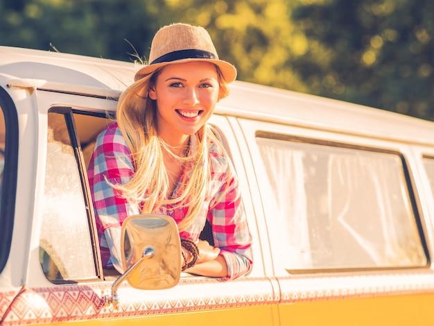 Genieten van een roadtrip. mooie jonge vrouw die naar de camera kijkt en glimlacht terwijl ze door het voertuigraam kijkt vehicle