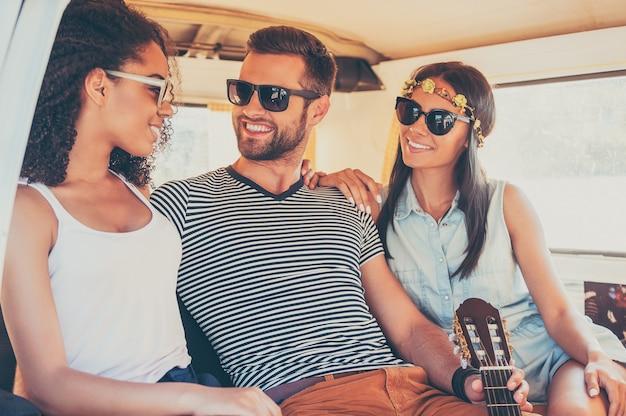Genieten van elk moment van hun roadtrip. drie jonge vrolijke vrienden die samen van de tijd genieten terwijl ze in de minibus zitten