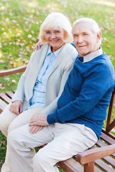 Genieten van elkaar. bovenaanzicht van een gelukkig senior koppel dat handen vasthoudt en met een glimlach naar de camera kijkt terwijl ze samen op het bankje zitten
