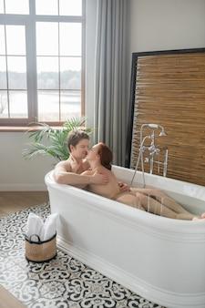 Genieten van elkaar. een man en een vrouw die samen in bad gaan en er leuk uit zien