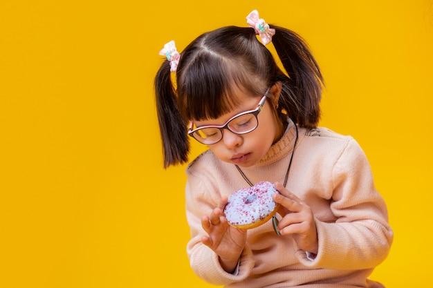 Genieten van gekleurde donuts. geconcentreerde jongedame met psychische stoornis bijten blauwe donut met roze hagelslag
