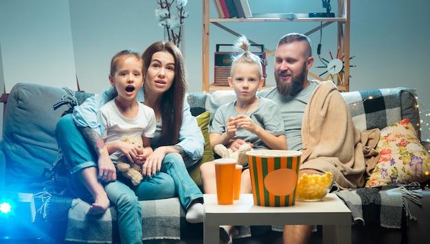 Genieten van. gelukkige familie die 's avonds thuis naar projector, tv, films met popcorn en drankjes kijkt. moeder, vader en kinderen brengen samen tijd door. thuiscomfort, moderne technologieën, emotiesconcept.