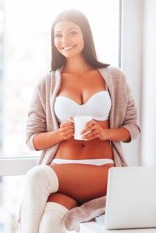 Genieten van goedemorgen. mooie jonge vrouw in lingerie en trui die koffiekopje vasthoudt en glimlacht terwijl ze bij het raam zit