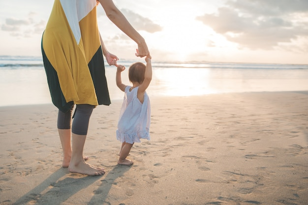 Genieten van haar eerste stap op het zand