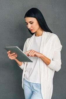 Genieten van haar nieuwe touchpad. mooie jonge vrouw die haar digitale tablet gebruikt terwijl ze tegen een grijze achtergrond staat