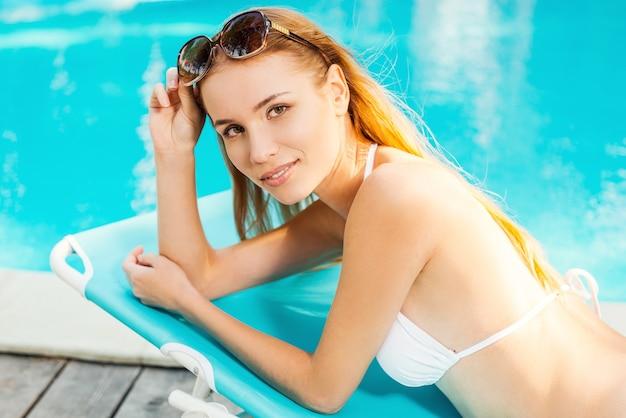 Genieten van haar vrije tijd bij het zwembad. mooie jonge vrouw in witte bikini ontspannen in de ligstoel bij het zwembad