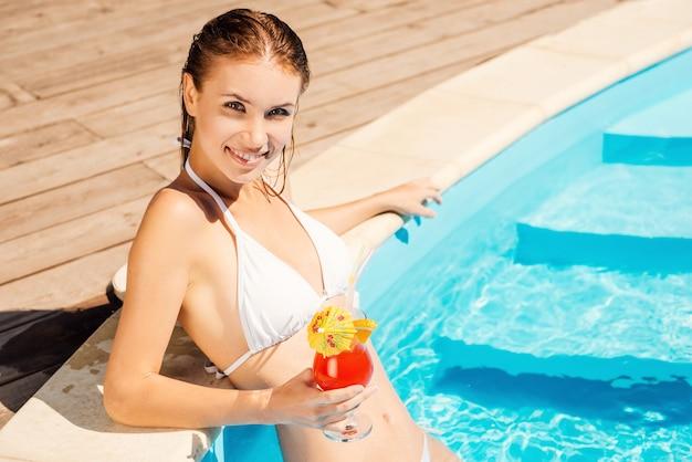 Genieten van haar vrije tijd bij het zwembad. schitterende jonge vrouw in witte bikini die cocktail vasthoudt en glimlacht terwijl ze bij het zwembad staat