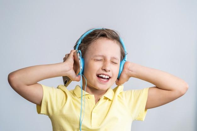 Genieten van het afspelen van liedjes in de koptelefoon. kleine jongen zingt op lied, grote muziekfan.