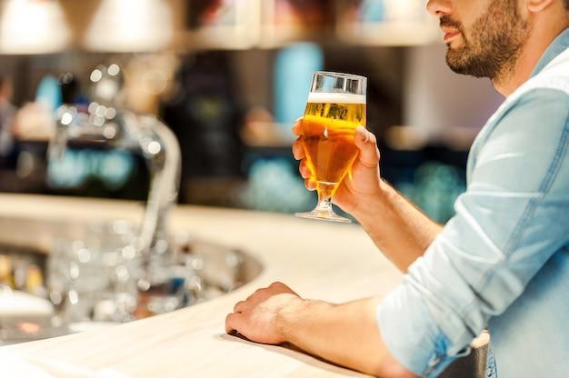 Genieten van het beste bier van de stad. bijgesneden afbeelding van een jonge man die een glas bier vasthoudt terwijl hij aan de bar zit