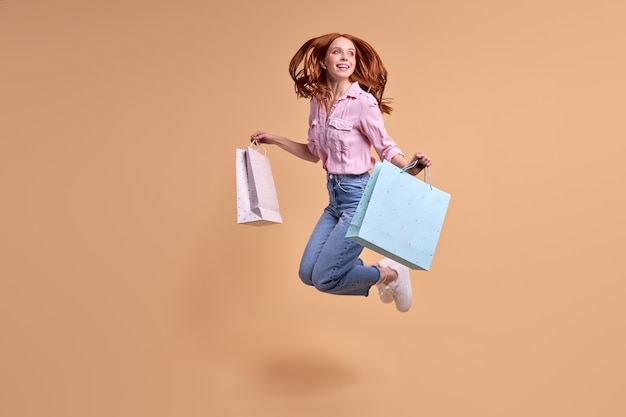 Genieten van het kopen van een vrolijke roodharige dame, blij na het winkelen, draag pakketten in een informele moderne st ...