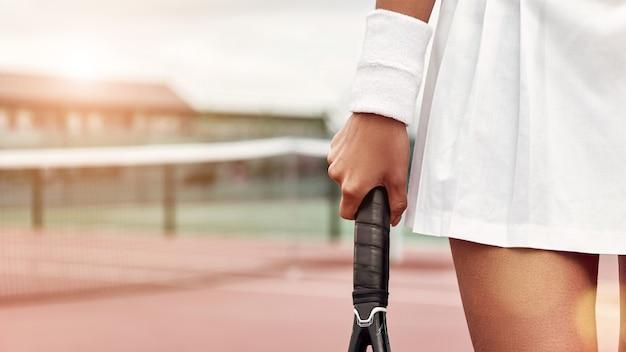 Genieten van het spelletje tennisser in rokje met racket in haar hand