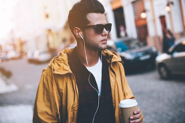 Genieten van het stadsleven. knappe jonge man in koptelefoon met koffiekopje tijdens het wandelen langs de straat van de stad