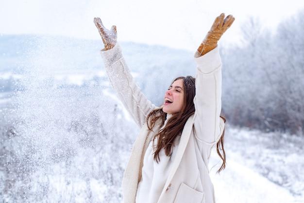 Genieten van het weer en de sneeuw. fijne winter. winter vrouw op besneeuwde achtergrond. . kerstmis-