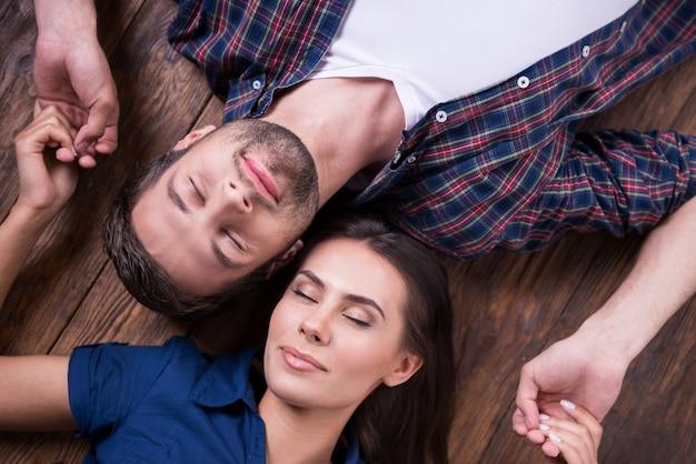 Genieten van hun nabijheid. bovenaanzicht van mooie jonge verliefde paar hand in hand en ogen gesloten houden terwijl ze samen op de hardhouten vloer liggen