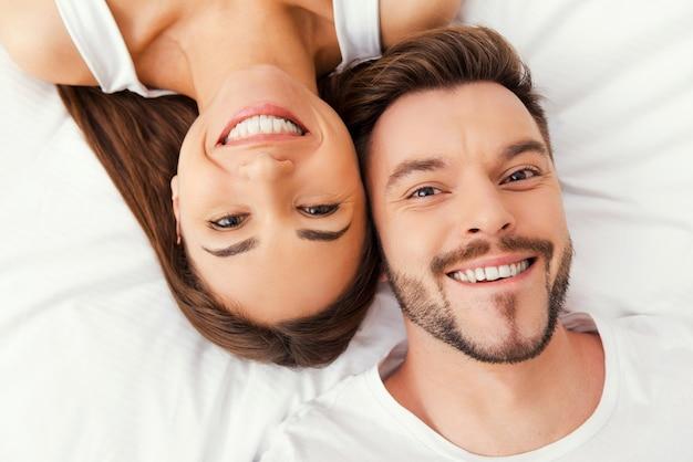 Genieten van hun tijd samen. bovenaanzicht van mooie jonge verliefde paar samen in bed liggen en glimlachen