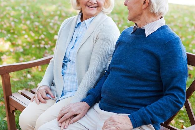 Genieten van hun tijd samen. close-up van een gelukkig senior koppel dat handen vasthoudt en elkaar aankijkt terwijl ze samen op de bank in het park zitten