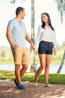 Genieten van hun tijd samen. volledige lengte van een mooi jong liefdevol stel dat langs de parkweg loopt en elkaar met een glimlach aankijkt