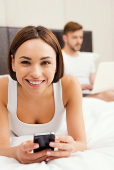 Genieten van hun vrije tijd thuis. mooie jonge vrouw die mobiele telefoon vasthoudt en glimlacht terwijl ze in bed ligt met man die op laptop op de achtergrond werkt