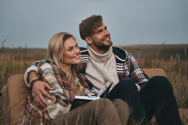 Genieten van hun vrijheid. mooie jonge paar omarmen en wegkijken met een glimlach zittend op het veld