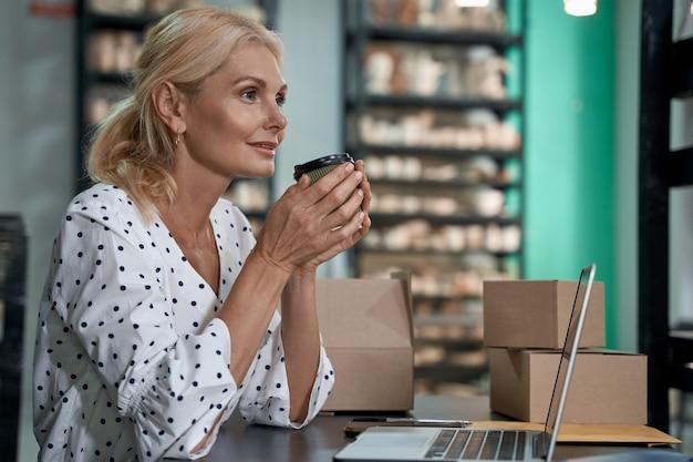 Genieten van koffie in de ochtend zijaanzicht van een mooie en gelukkige vrouwelijke ondernemer of bedrijf