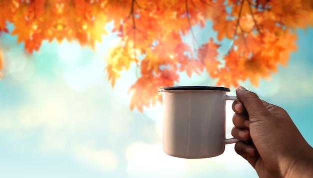 Genieten van koffie in herfst- en herfstseizoen. hand verhoogd een warme koffiekop in de lucht op zonnige dag. pov-opname. focus op beker. wazig maple tree als achtergrond