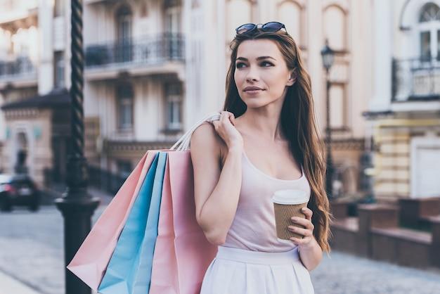 Genieten van koffie na een dagje winkelen. mooie jonge vrouw die boodschappentassen draagt en een koffiekopje vasthoudt terwijl ze over straat loopt