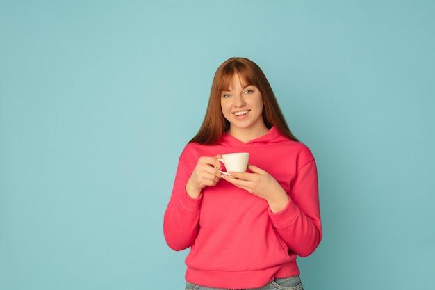Genieten van koffie, thee. portret van de blanke vrouw op blauwe studio oppervlak met copyspace. Gratis Foto