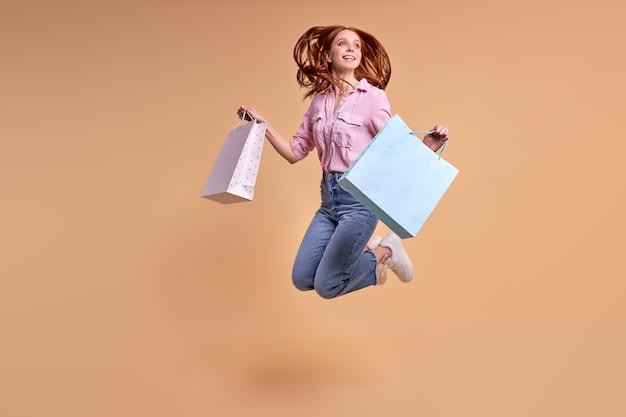 Genieten van kopen. vrolijke roodharige dame blij na het winkelen, pakketten dragen, in casual moderne stijlvolle spijkerbroeken, springen, plezier maken. geïsoleerde pastel gele achtergrond. kopieer ruimte