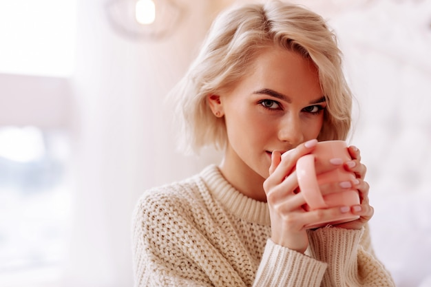 Genieten van lekkere thee. close up van jonge mooie vrouw met bob knippen genieten van lekkere thee in de slaapkamer
