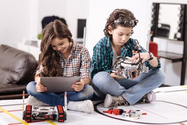 Genieten van nieuwe apparaten. positieve betrokken geamuseerde kinderen die thuis zitten en gadgets en apparaten gebruiken terwijl ze plezier hebben Premium Foto