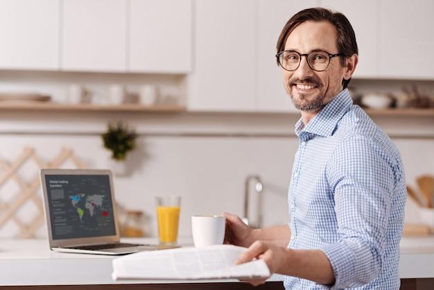 Genieten van nuttig weekend. begaafde positieve inventieve zelfstandige zakenman om thuis te zitten en sap te drinken tijdens het gebruik van laptop en het lezen van de krant