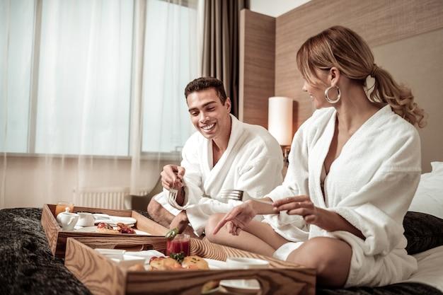 Genieten van ontbijt. man en vrouw die witte badjassen dragen die van ontbijt in hotelkamer genieten