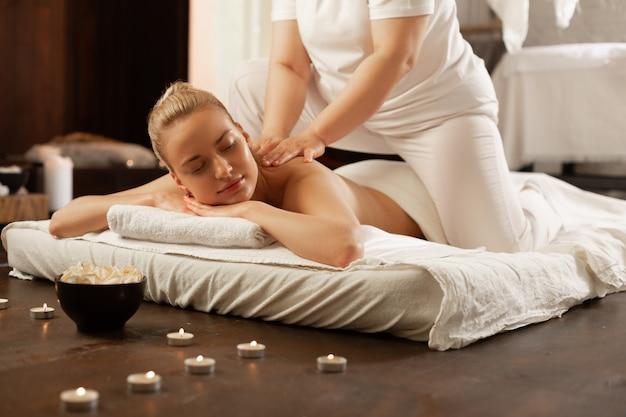 Genieten van procedures. mooie blonde klant die blij is met ervaren massagemeester tijdens een bezoek aan het spa-centrum