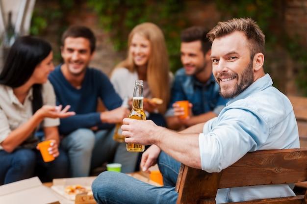 Genieten van tijd met vrienden. gelukkige jonge man die een fles met bier vasthoudt en naar de camera kijkt terwijl zijn vrienden op de achtergrond met elkaar praten