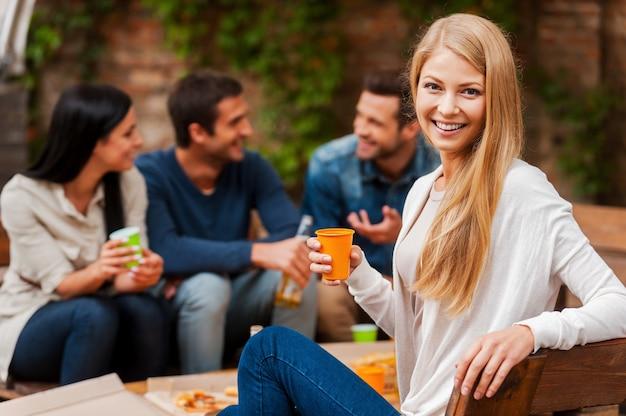 Genieten van tijd met vrienden. glimlachende jonge vrouw die glas vasthoudt en naar de camera kijkt terwijl haar vrienden op de achtergrond met elkaar praten