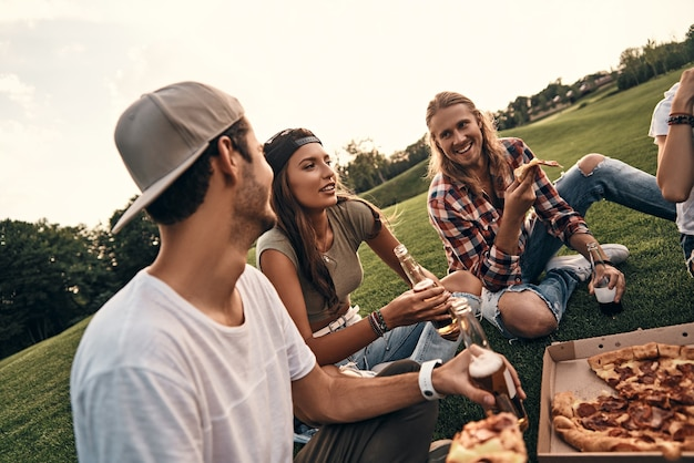 Genieten van tijd met vrienden. groep jonge lachende mensen in vrijetijdskleding die genieten van pizza en bier terwijl ze buiten op het gras zitten