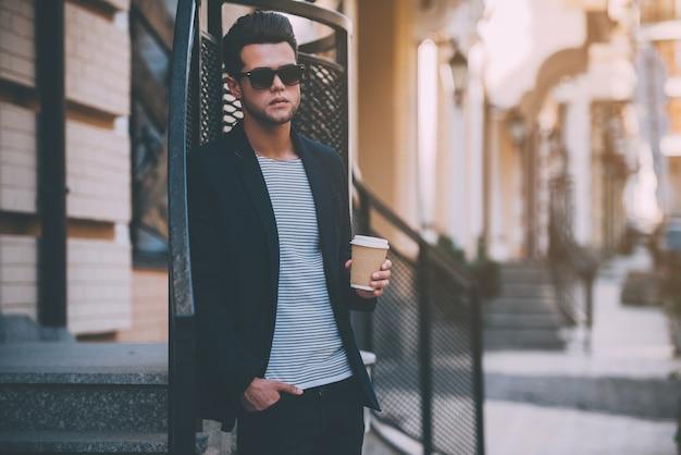 Genieten van verse koffie. knappe jonge man in slimme vrijetijdskleding met koffiekopje terwijl hij op straat staat