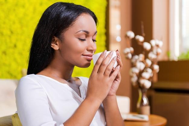 Genieten van verse koffie. zijaanzicht van mooie jonge afrikaanse vrouw met koffiekopje in de buurt van neus