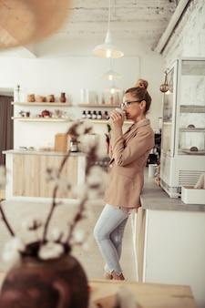 Genieten van vrije tijd. slimme lachende vrouw die in de keuken staat en koffie drinkt tijdens haar koffiepauze.