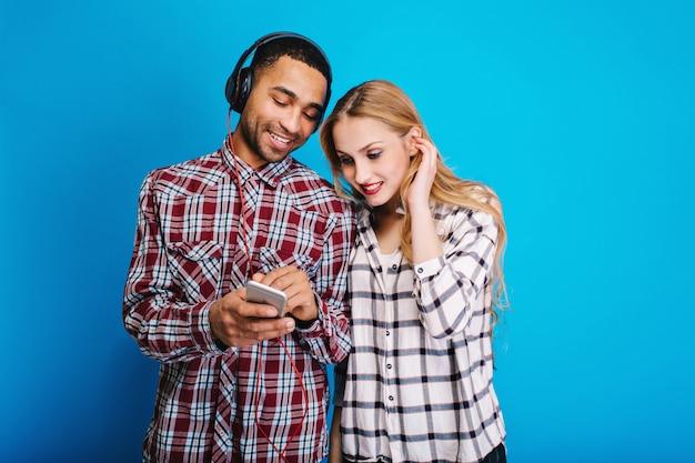 Genieten van vrije tijd van een leuk stel jonge stijlvolle knappe man en vrouw die samen plezier hebben. luisteren naar muziek, weekends, relaxen, liedjes, modern.