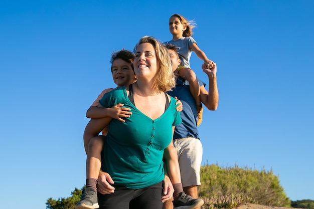 Genieten van wandelen op het platteland en gelukkige familie. twee kinderen rijden op ouders rug en nek. lage hoek. natuur en recreatie concept