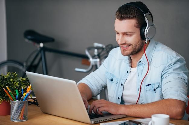 Genieten van werk en goede muziek. vrolijke jonge man in koptelefoon luisteren naar de muziek
